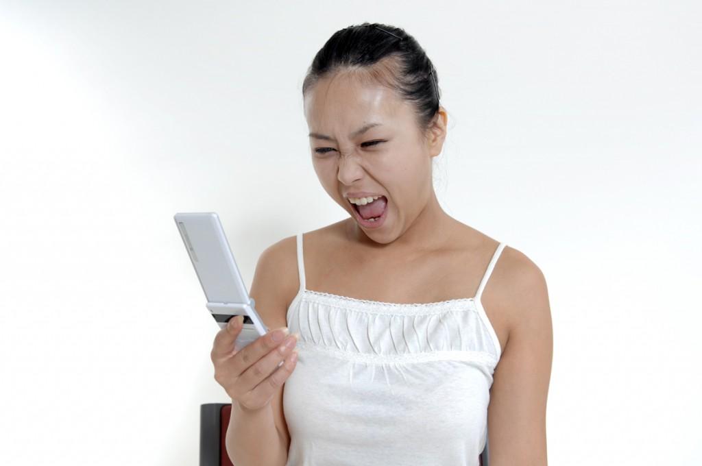 携帯に向かって顔をゆがめる女性