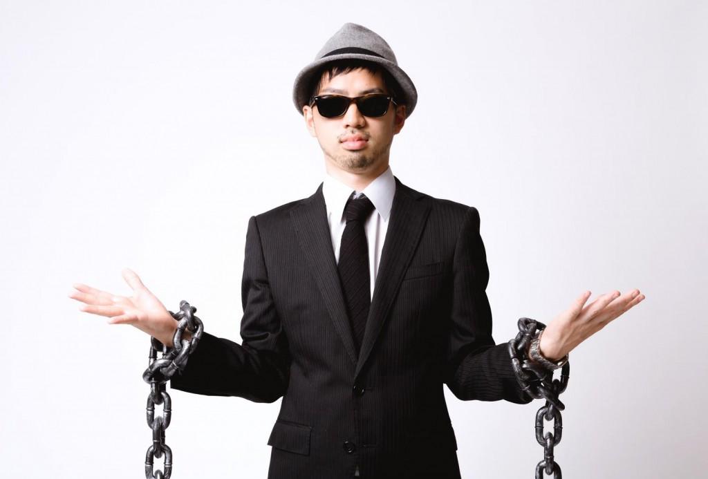 両手を鎖でつながれたサングラスをかけた男性